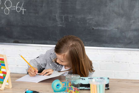 The schoolgirl solves the task. The girl writes in a notebook with a pen. Primary school.