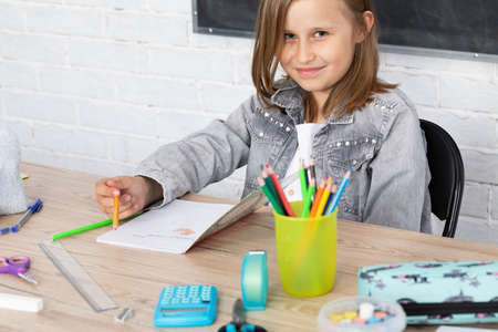 Schoolgirl happy that she is at school in a drawing lesson. He is smiling at the camera. Joyful girl.