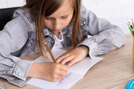 The girl in the lesson was given the task of drawing a teddy bear. The young schoolgirl draws with crayons in a school notebook.