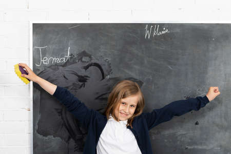 The student, while wiping the chalkboard, raised her hands and turned toward the students in the classroom