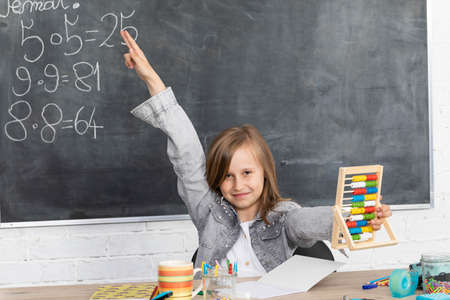 The girl raised her hand in class. The student knows the solution of the task given by the teacher. Eager to answer. Фото со стока