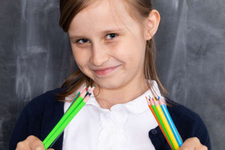 Primary school. The girl sits on a bench and holds crayons in her hand.