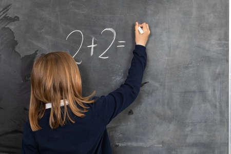 He writes on the chalkboard with chalk. Math problem. A girl at the chalkboard. Reklamní fotografie