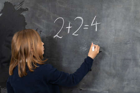 He writes on the chalkboard with chalk. Math problem. A girl at the chalkboard.