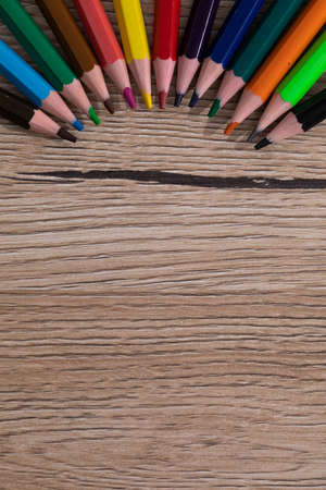 New unused colored pencils. Each of them is sharp and accurate. Wooden desk top. Zdjęcie Seryjne