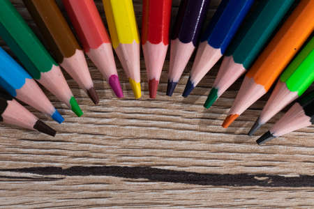 New unused colored pencils. Each of them is sharp and accurate. Wooden desk top.