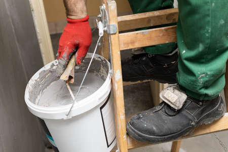 A professional construction worker soaks a paint roller in a bucket full of liquid moisture insulation. During work. Close-up view.