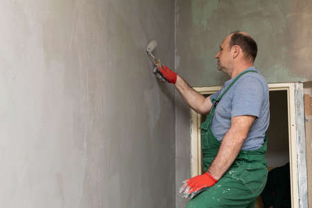 Bathroom renovation. Construction worker. Mineral moisture insulation. During work.