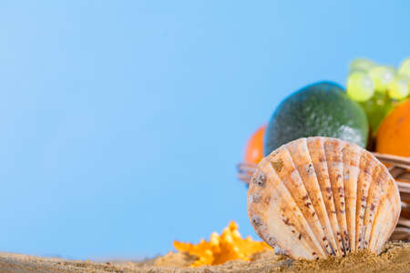 Blue sky over the sea beach. Ripe southern fruits lie in the basket. Sea shore of a sandy beach. Stock Photo