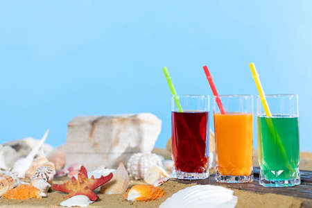 Fresh fruit juice in a tall glass. Shore of a sandy beach on a cool sea.