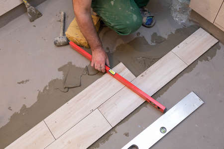 Spirit level - a device for checking the correctness of works performed in relation to the level. A professional construction worker. Kneeling.