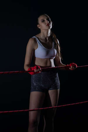 A tightly clenched hand on the boxing ring. A player strongly focused before her life fight in MMA.