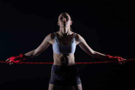 The athlete is based on the red rope of the boxing ring. A determined woman stands in the ring ready to start the fight.