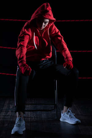 A lost fight of a strong MMA player. He is sitting in a chair. Right after losing the fight. Sad woman after a fight in the ring. In a hoodie. 免版税图像