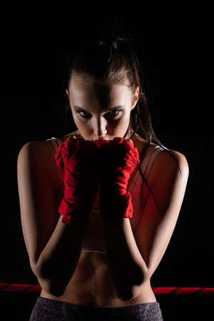 The head is hidden behind the strong guard of a professional sportswoman. A strong and athletic woman in the ring of sports which is MMA.
