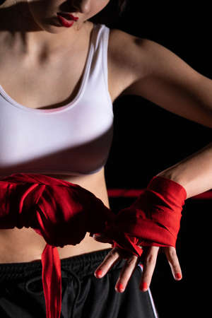 A woman prepares for an MMA fight, wrapping her hands in a special boxing bandage. Strong woman. The inevitable fight in the ring.