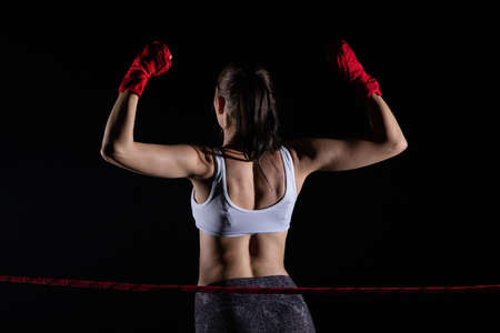 The MMA fighter won her first fight. The woman raised her hands in evidence of winning the fight. Banco de Imagens