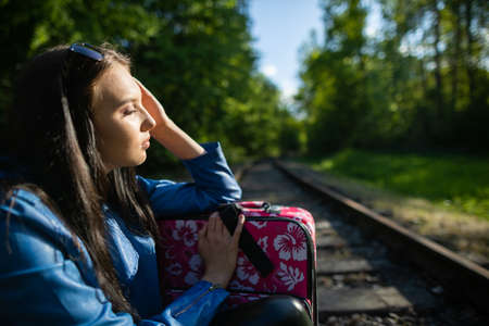 A young woman tired from hiking is sitting on the railway tracks. A holiday adventure without money and on foot all the time.