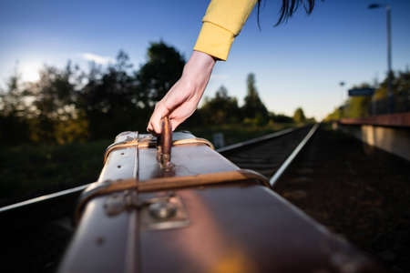 Close-up shots of an old travel suitcase held by the handle by a womans hand while walking along the railroad tracks in the late afternoon...