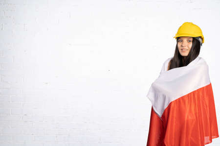 A teenager wearing a protective helmet threw on her shoulders and back the national symbol of Poland, which is the countrys flag.