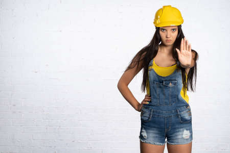 A female construction worker stops traffic on a construction site. Young lady engineer. The woman shows to stop.