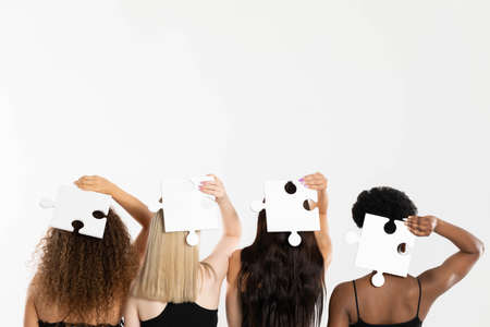 Different ethnicity and the same genes represented by matching puzzle pieces. Four women turned away.