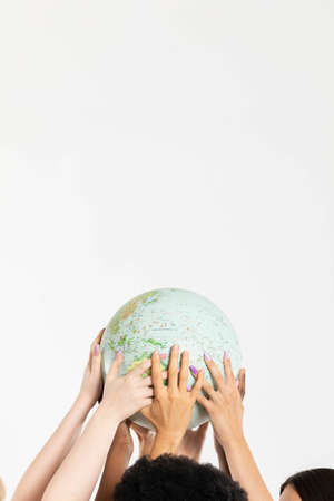 A large globe with all continents is supported by female hands of various races, symbolizing unity, acceptance and racial tolerance. Foto de archivo