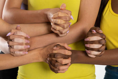 Clenched fingers into a common fist. A symbol of brotherhood and friendship that grows despite childhood differences in skin color.