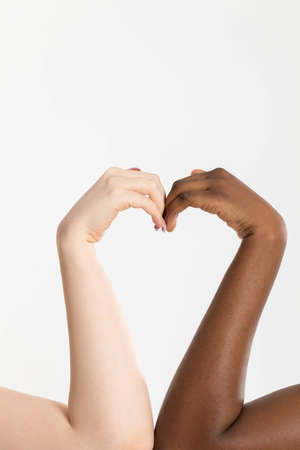 The shape of the heart as a symbol for all people and the world who are in love and their other half is of a different race. Dark and light complexion on the hand. Stock Photo