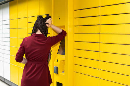 The girl stands in front of the parcel locker and waits impatiently for the machine to open her locker with the ordered package. Banque d'images