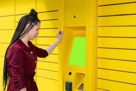 The girl stands in front of the parcel locker and waits impatiently for the machine to open her locker with the ordered package.