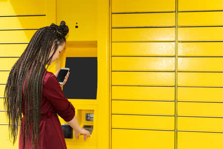 A teenager operates a machine for collecting various types of parcels. African braids.