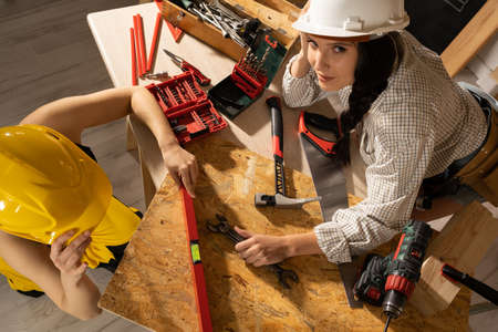 The blonde puts a red spirit level to the table top and the brunette checks if the indications are correct. Stock Photo