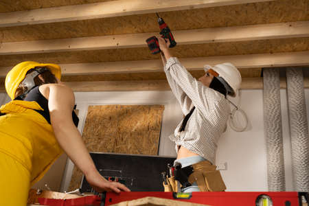Work with power tools on the construction site. Two young girls in working clothes work together on a construction site finger. Stockfoto