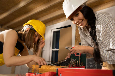 Smiling girls in the workshop while searching for the right wrench to tighten the screws in wooden beams.