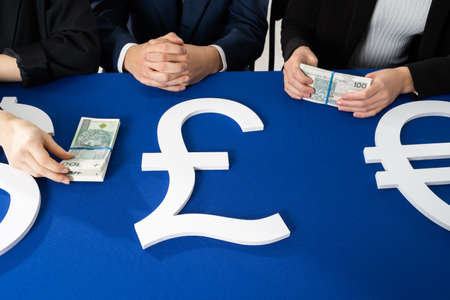 The three-person commission divides the money intended for the needy. On the blue table lie bundles of banknotes in the face value of one hundred Polish zlotys. 免版税图像