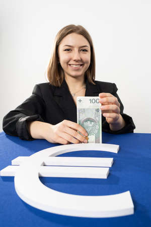 Smiling young adult at the currency service counter of the national bank. A gifted girl in a responsible position. 免版税图像