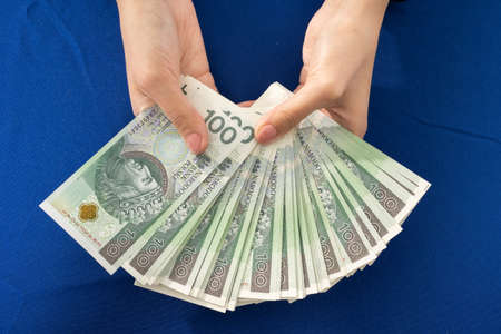 Green banknotes held in young female hands. Blue tablecloth on the table.