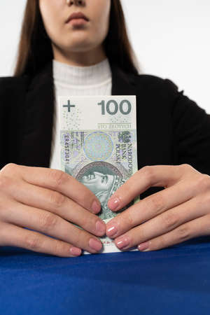 Young adult sitting at the table with money in hand. The ban employee is waiting for the customer who ordered the burn from his account. Reklamní fotografie