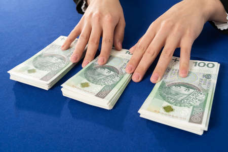 Banknotes neatly placed on a blue tablecloth are waiting for the person who decides to take out a cash loan. 免版税图像