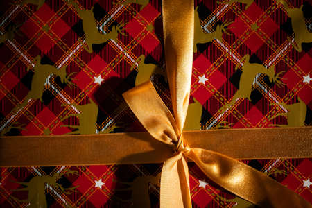 Prepared for giving a gift with a beautiful golden bow for a husband or wife on Christmas Day. Gift wrapped.