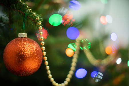 A shiny ornament in the shape of a round Christmas ball attached to a Christmas tree on a Christmas background with cork lights.