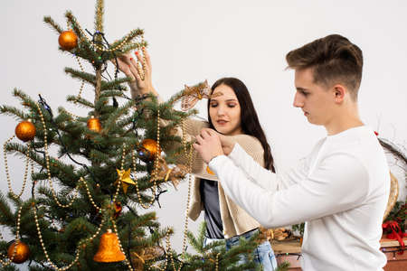 Couple in love while decorating the Christmas tree for Christmas. Smiling young people.