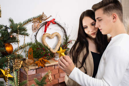 The bride and groom will continue to decorate the Christmas tree. Decoration of a Christmas tree for Christmas in December.