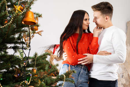 The fianc e hugged his fianc e and looks her straight in the eyes as he stands by the decorated Christmas tree. December Christian holidays.