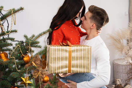 The fiance lifted his partner up in a fit of joy. Lovers flirt in a decorated living room at home. December Christian holidays.