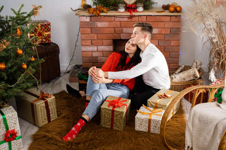 The bride and groom, sitting by the Christmas tree, communicate their feelings in body language. Lovers flirt in a decorated living room at home. December Christian holidays.