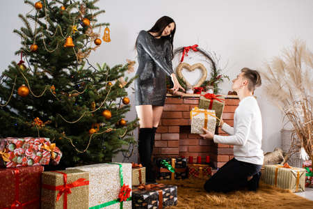 An unexpected gift from a fianc e while decorating a Christmas tree for Christmas. December Christian holidays. Shiny black dress. Stock fotó