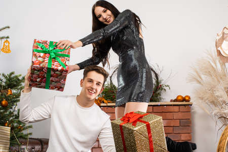A whole mountain of gift packages are lying next to a decorated Christmas tree in the living room. Shiny black dress. December Christian holidays.