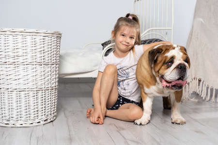 An old and fat dog and a tiny and young girl sit on the floor by the bed in the bedroom. A breed with a brown coat with white patches.
